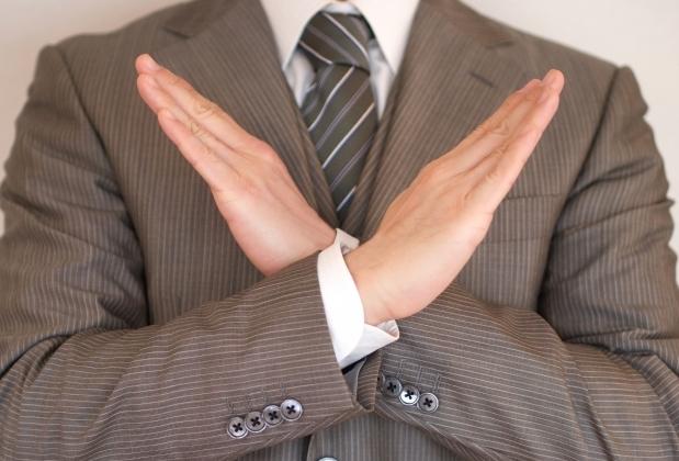 胸元で腕でバツ印を作るスーツ姿の男性の上半身