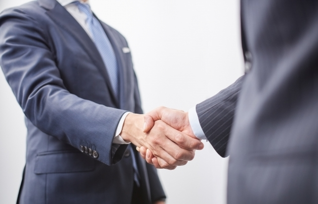 握手するスーツ姿の二人の男性