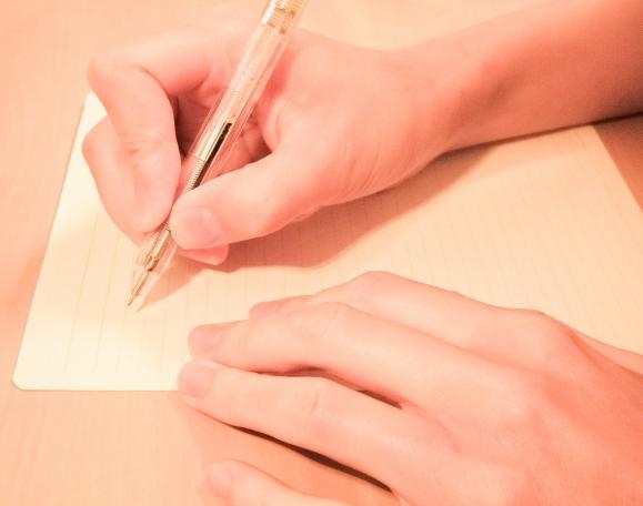 木の机の上で手でペンを持って黄色の紙の上に文字を過去としている写真