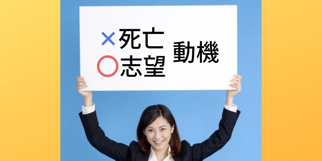 スーツ姿の女性が持った白い看板に書かれた「志望動機」という文字