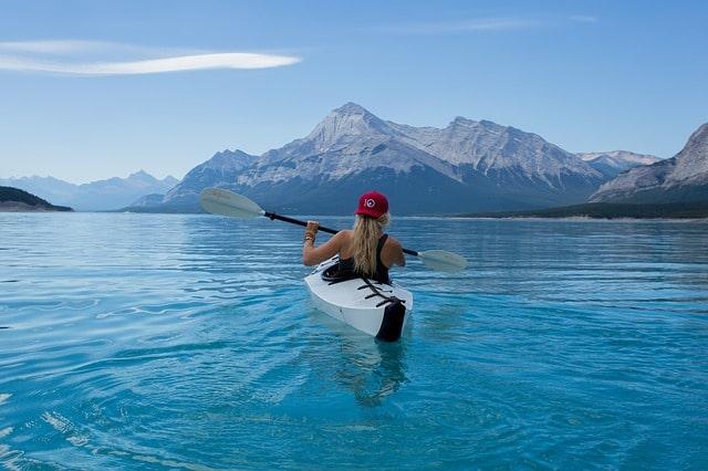 山に向かってカヌーを漕いで進む女性