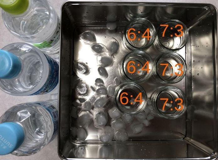 3つのペットボトルと氷水を張った金属の箱と6つのガラスコップ