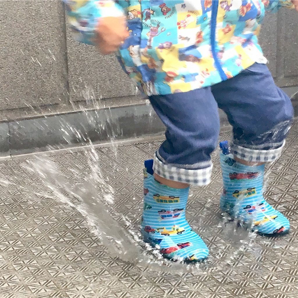 水たまりに勢いよくジャンプする3歳の男の子の足元の水しぶき