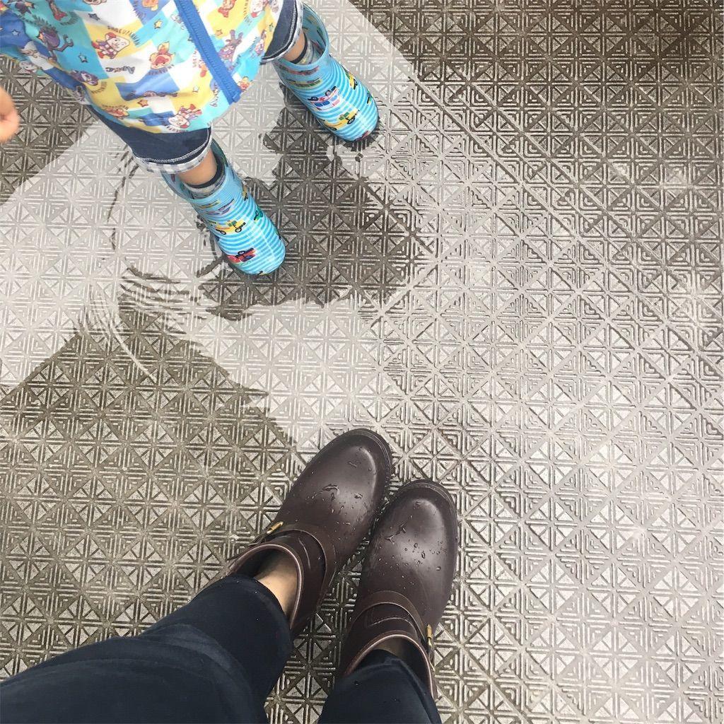 雨の日の3歳の男の子と母親の長靴