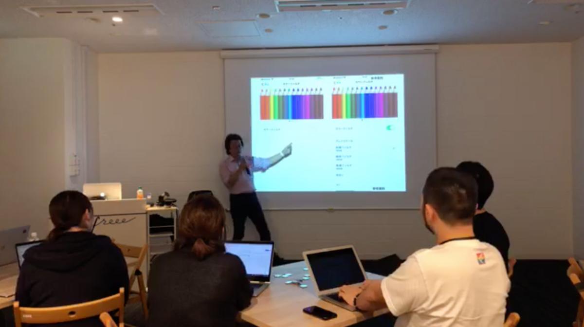 写真:伊賀さんによるスライドを使ったプレゼン。iOSの色の調整画面を表示している。
