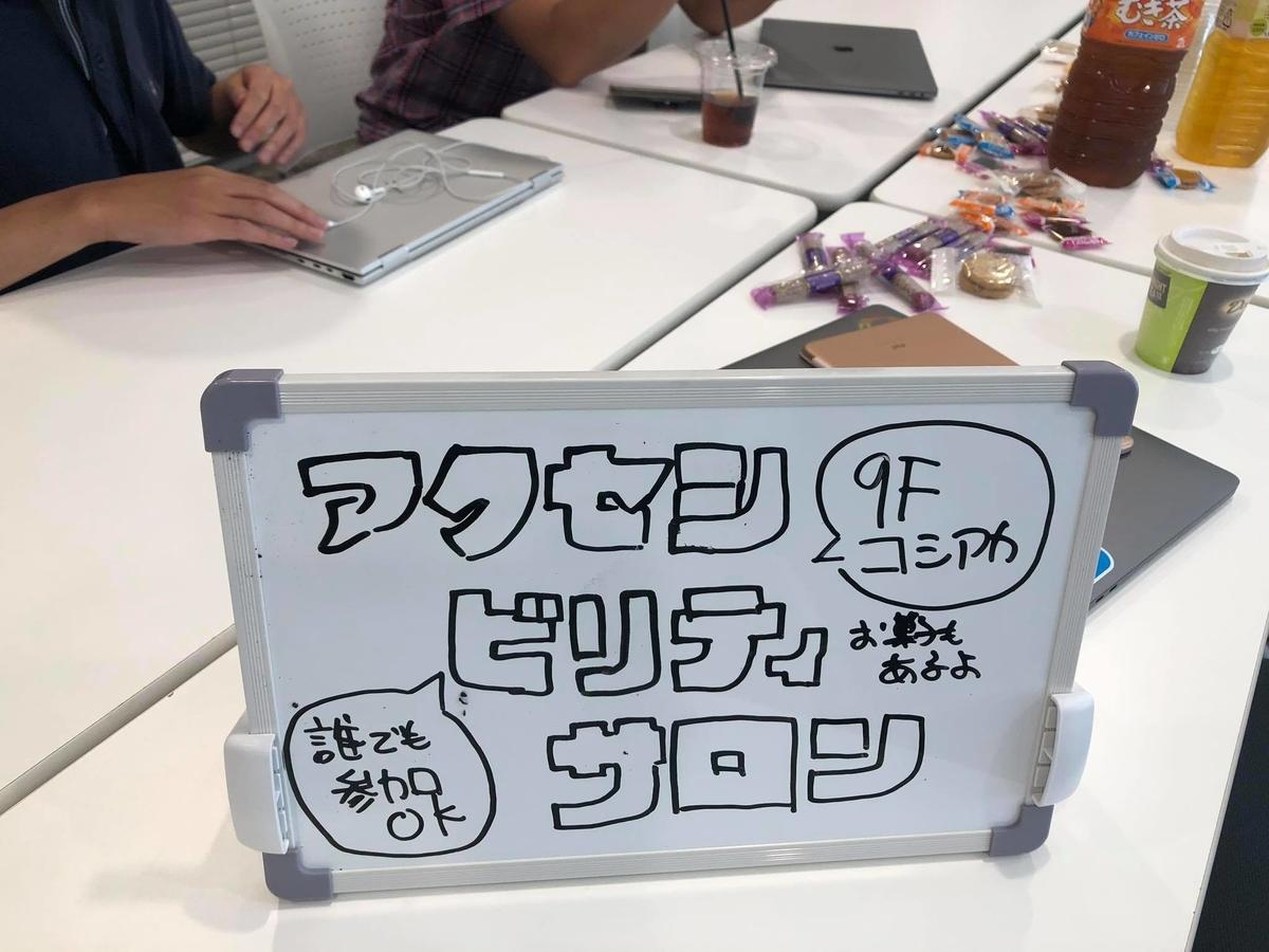 写真:小さなホワイトボードにアクセシビリティサロンの題字が書かれている。その裏にはお菓子や参加者の手が見える。
