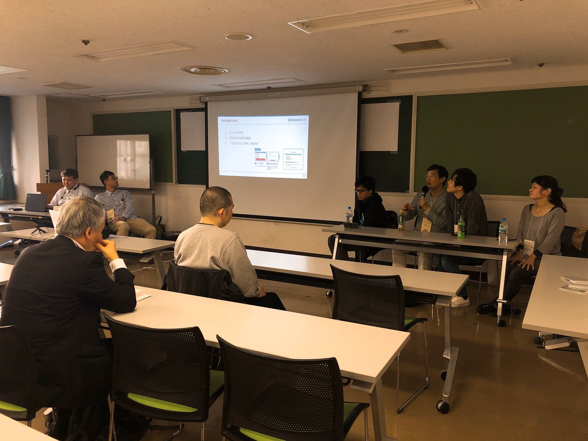 写真:NVDA相談会の会場の様子。着席する参加者と、登壇者、スクリーン。