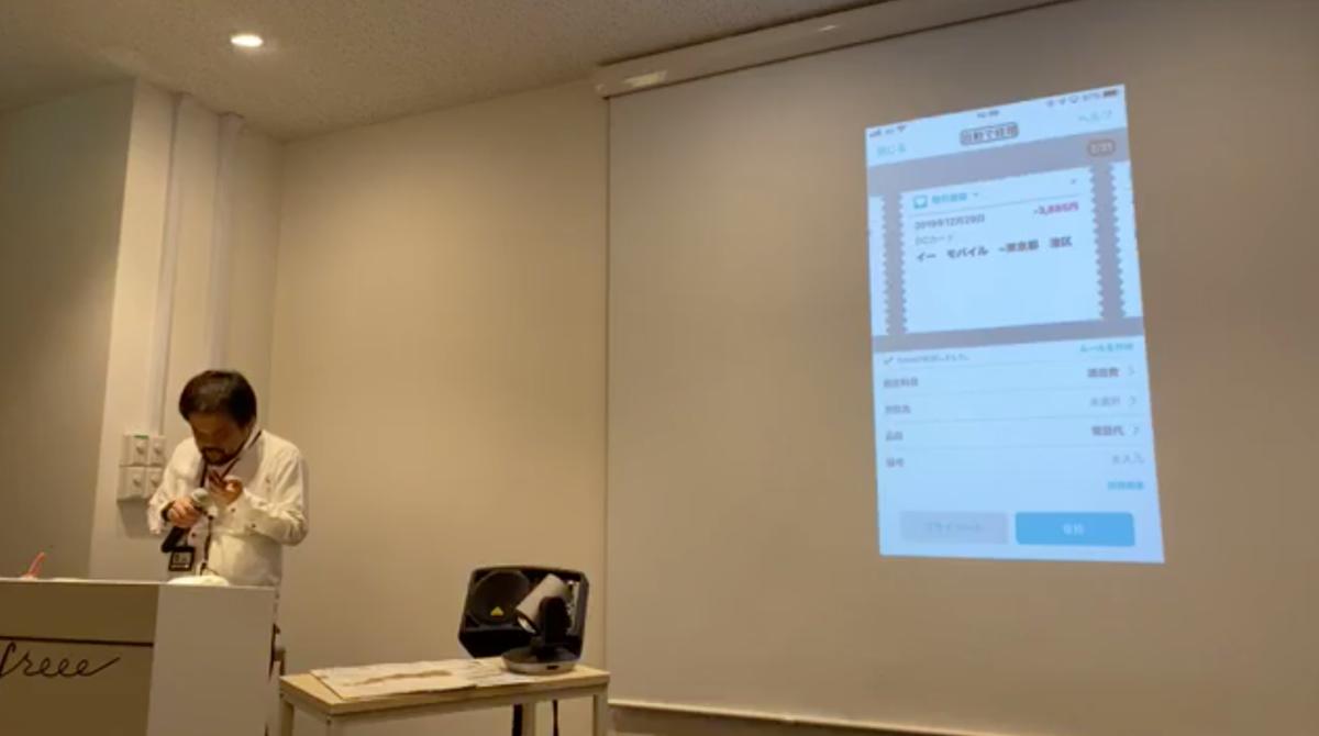 写真:中根さんが自動で経理のデモをしている。手元のiPhoneで「自動で経理」を操作した結果が、スクリーンにミラーリングされている。