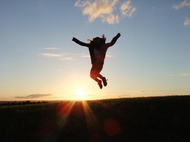 太陽に向かって飛び跳ねる人