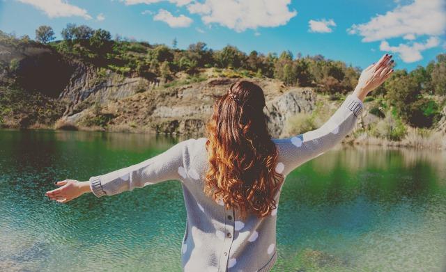 湖を前にして手を広げる女性