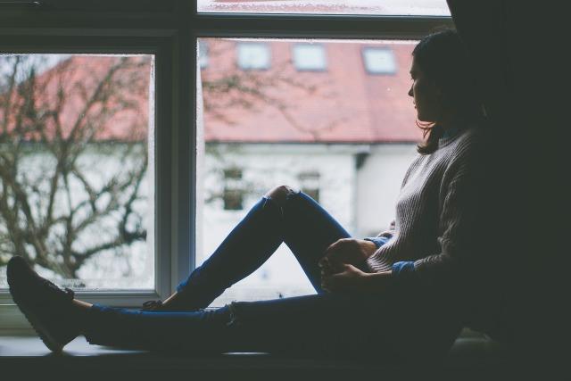 窓を見つめて考える女性