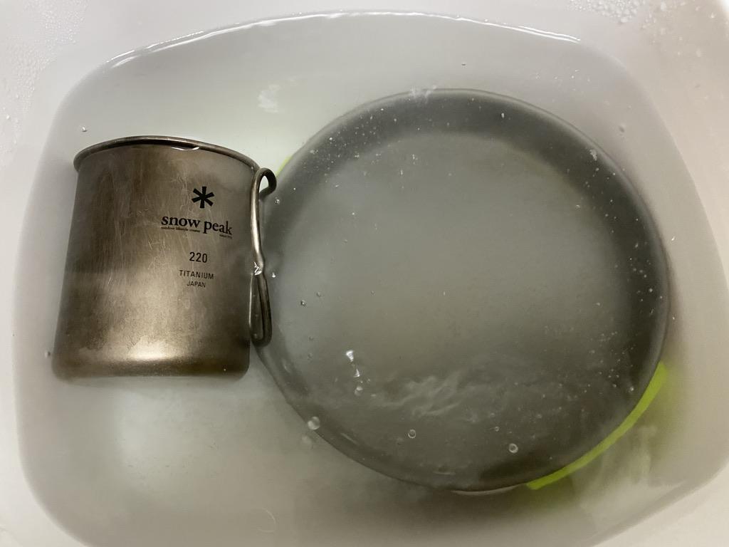容器に入った重曹水にクッカーとチタンマグを浸した様子