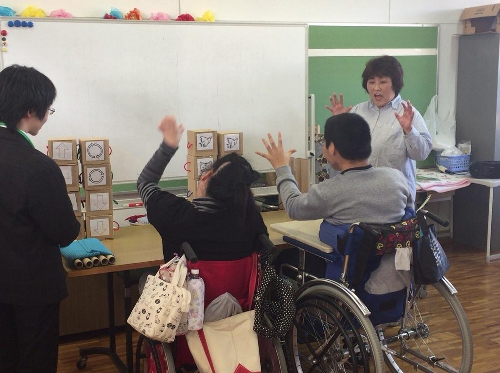 プログラムキューブでプログラミングしている高等部の生徒二人の後ろ姿、教師とメンターが見守っている。