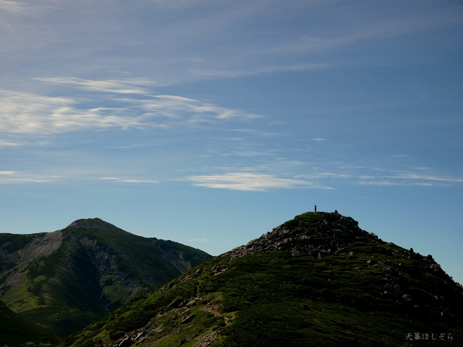 北アルプスの頂上に立つハイカー