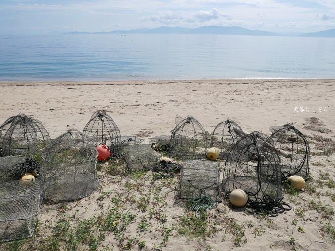 砂浜と魚獲りのカゴ