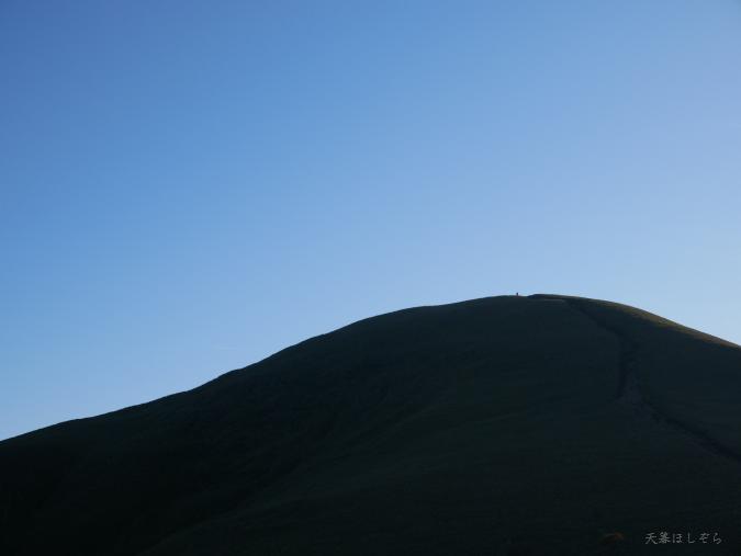山頂に立つソロのハイカー