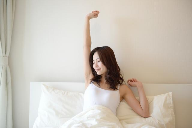 起き抜けに背伸びをする女性