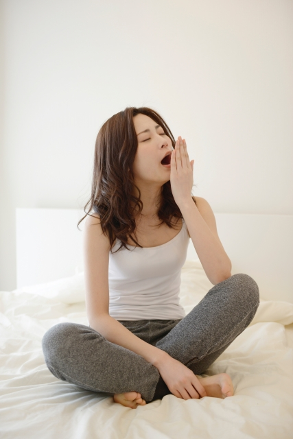 ベッドの上で胡坐をかく女性
