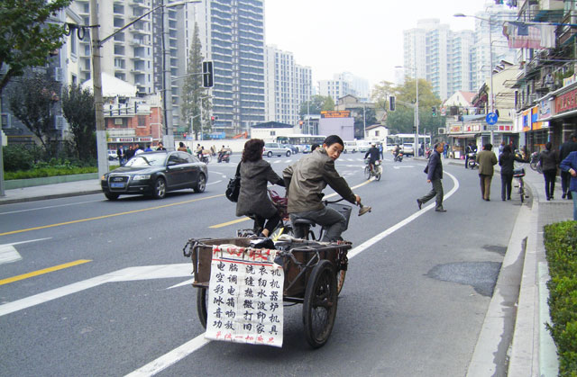 上海の貧富の差。リヤカーの対向車線にはアウディ。