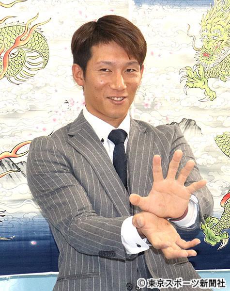 契約を更改し、名前にちなんだ竜の絵柄壁掛けの前でポーズを決める西川選手