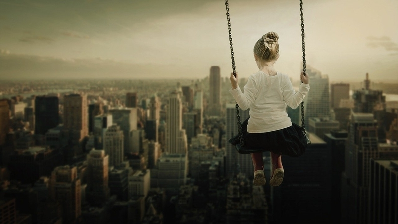 高いところにあるブランコから世の中を見下ろす女の子
