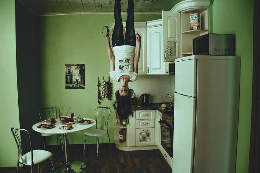 冷蔵庫の近くで天井に逆さまに立って呆然とする女性