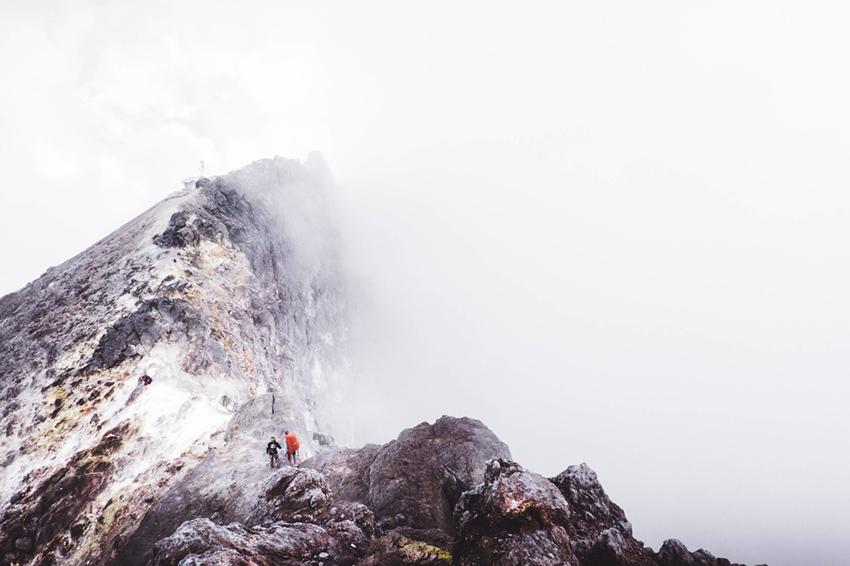 雲で先が見えない山を登っているふたり