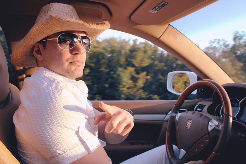 車の運転席に座って指を指す男