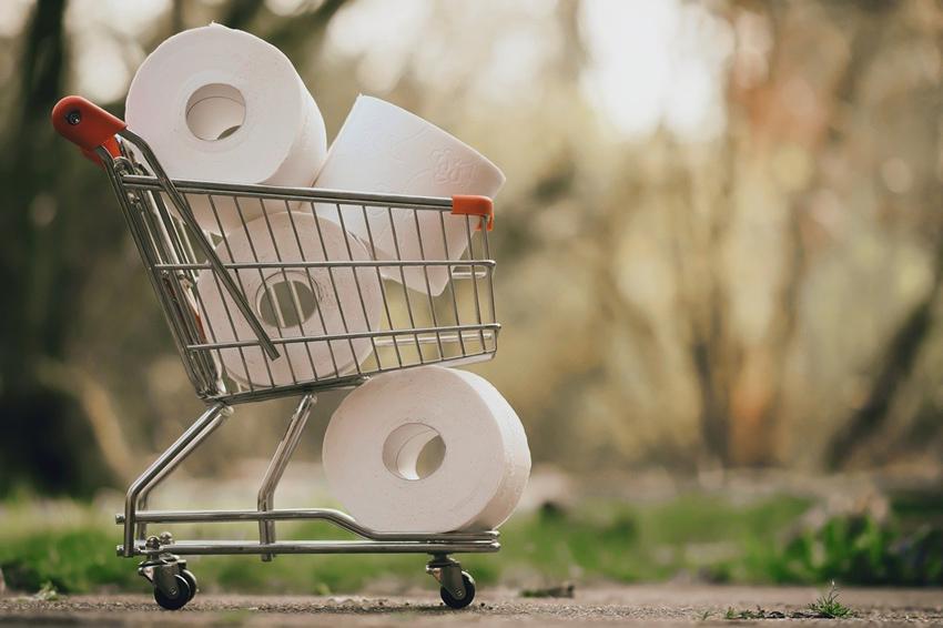 ミニチュアのショッピングカートに積まれたトイレットペーパー