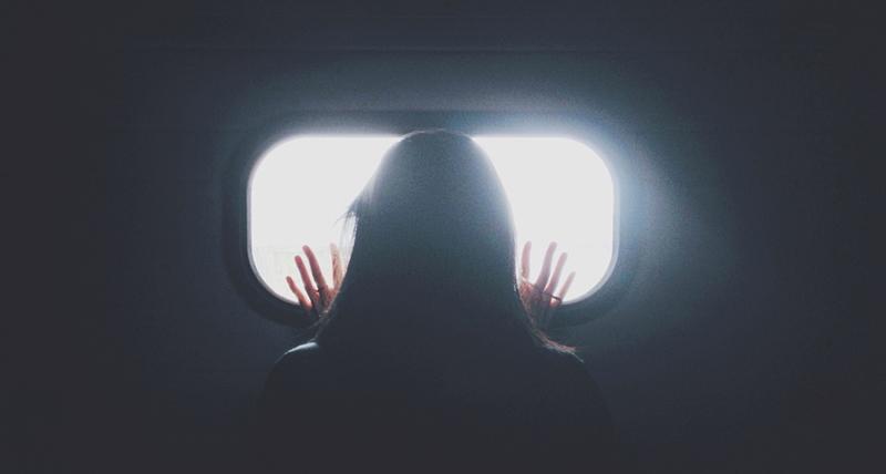 明るい窓の外をのぞく女性