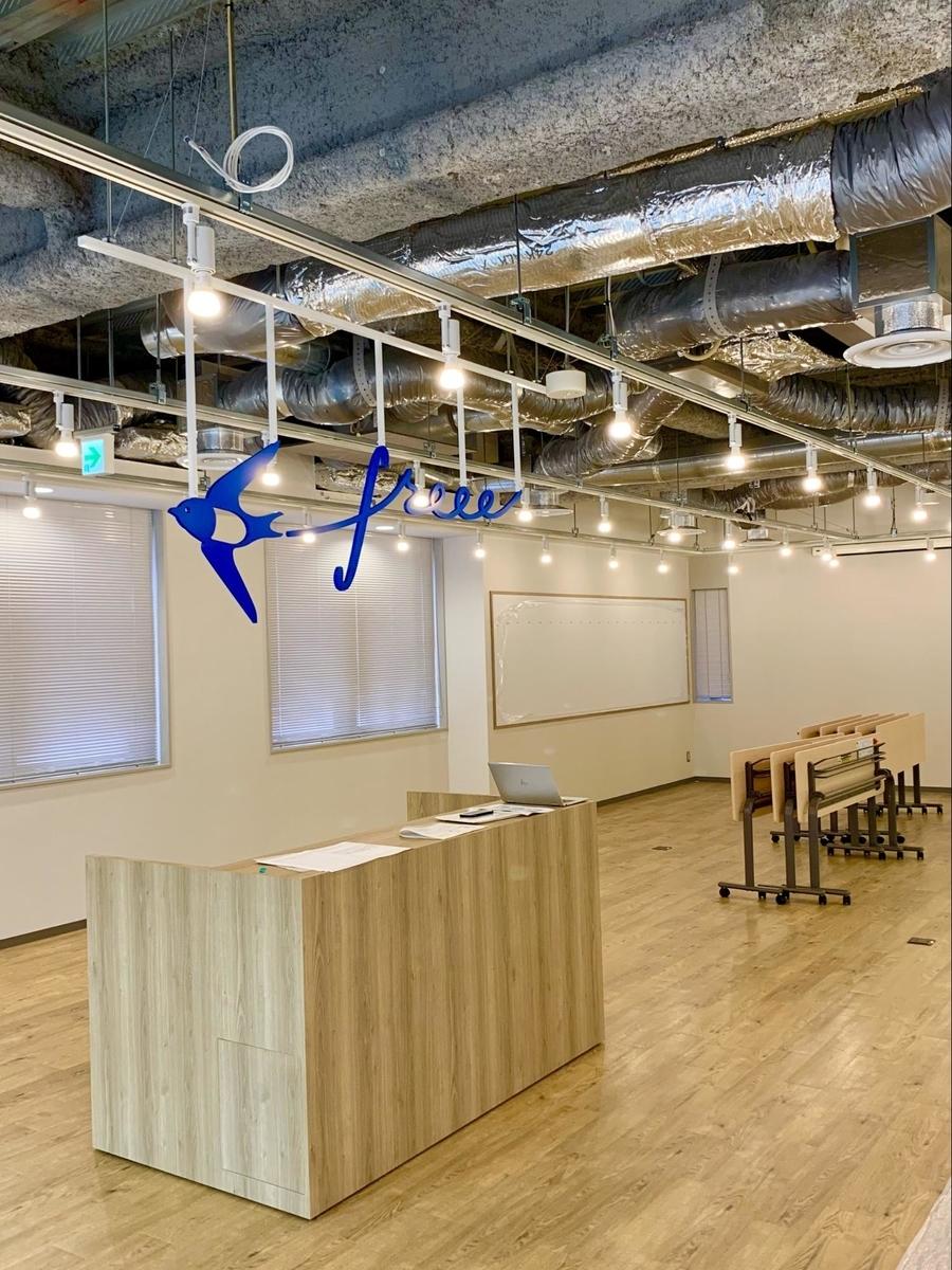休憩スペースのカウンターの上にfreeeのロゴマークが天井から吊り下げられている