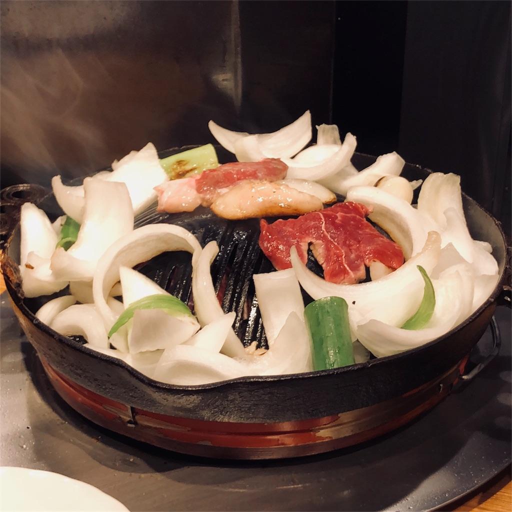 ジンギスカンの写真。お肉の周りを彩る玉ねぎはまるで白い薔薇のように美しい