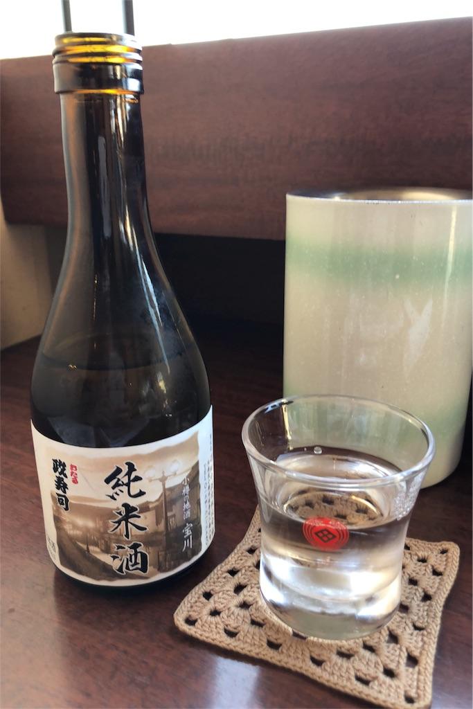 小樽の水を使った日本酒「宝川」のミニボトルと、それがなみなみに注がれているグラスの写真。