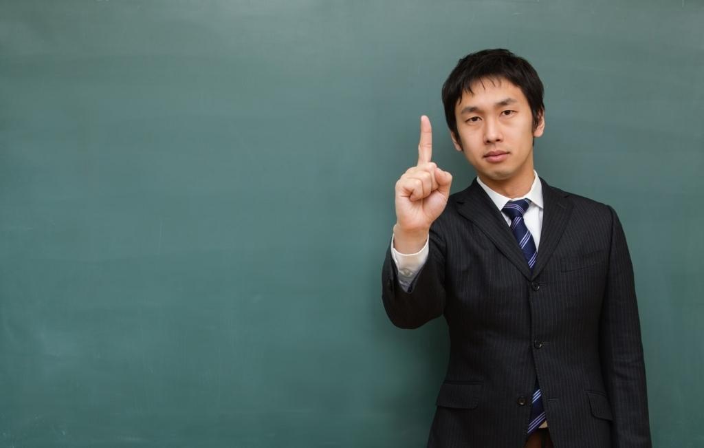 黒板の前に立つ塾講師
