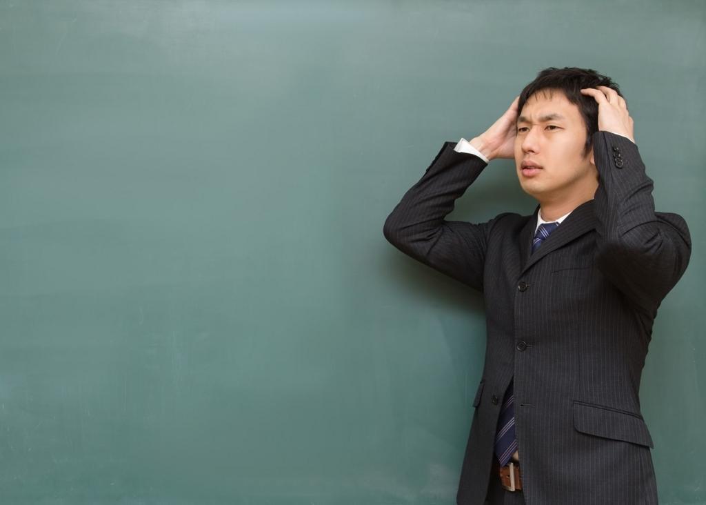 頭を抱える男性講師