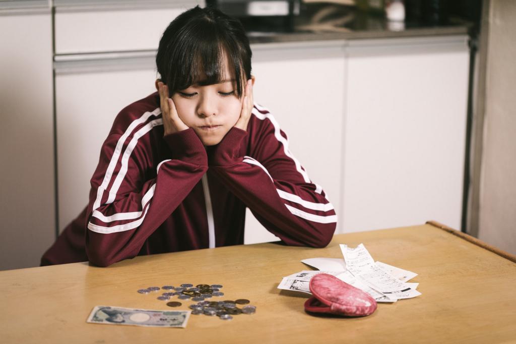 お金を見て悩む女性