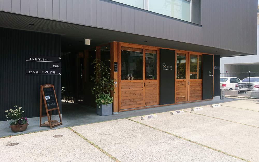 お店の外観は、黒っぽいコンクリートの壁に大きなガラス窓で木目調の扉