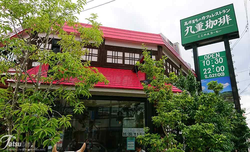 緑の看板と赤い屋根の建物が一際目立つお店が見えます。
