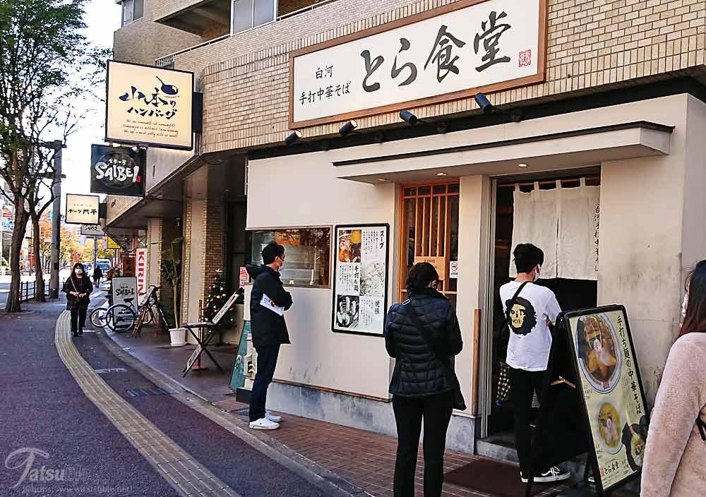 お店の傍までくると行列ができている場所があり、看板に「とら食堂」と書かれています。