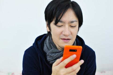 スマートフォンを操作している男の人の写真