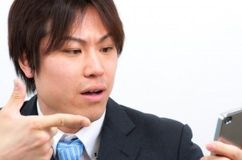 スマホを指さしている男の写真