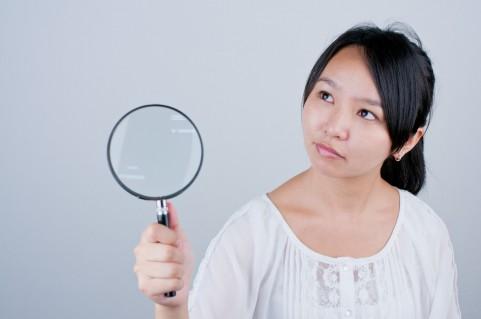 虫眼鏡を持つ女の人の写真