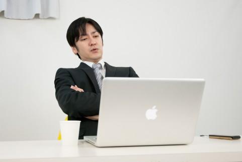 PCを眺めている男の人の写真