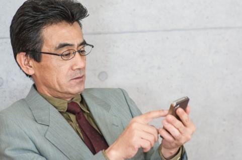 スマホを操作する男の人の写真
