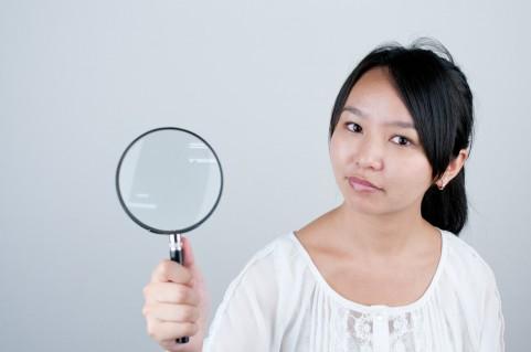 虫眼鏡を持っている女の写真