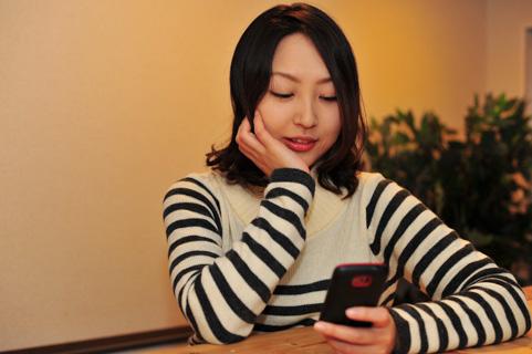 スマートフォンを持って微笑んでいる女の写真