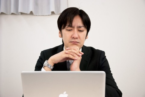 PCを眺めて考えている男の人の写真
