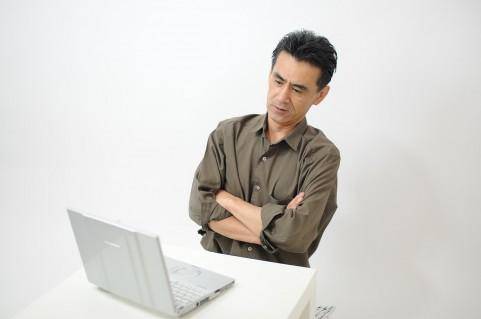 PCを見て怪しんでいる男の写真