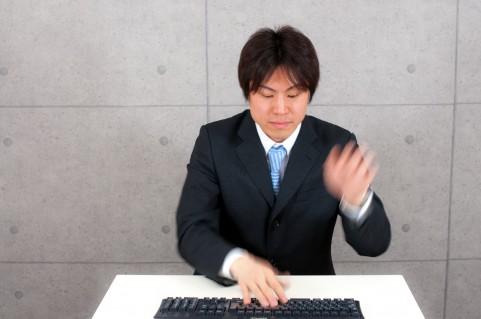 キーボードを叩いている男の写真