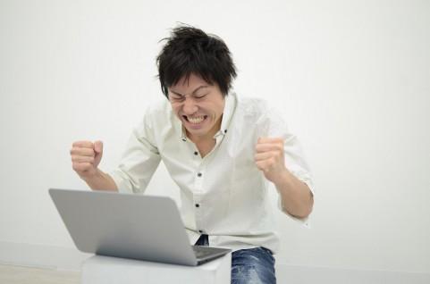 PCを見て喜んでいる男の写真